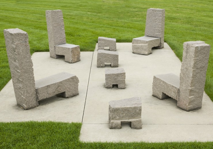 Stone chairs and stools atop a stone inset on the grass of the garden.
