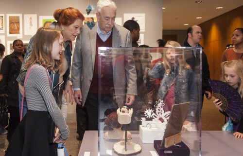 Family looking at art in glass case.